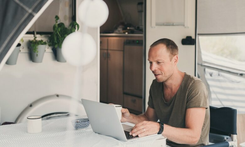 Image of a man drinking coffee while using his computer outside his RV